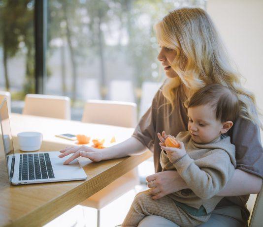 Une professionnelle utilise des outils de télétravail en compagnie de son enfant.