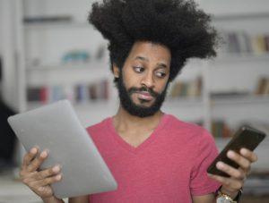 Un internaute lit son guide du référencement Web sur son téléphone et sa tablette